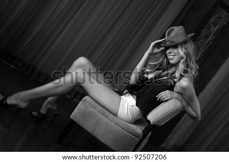 Portrait of beautiful blonde girl wearing hat and sitting in  chair