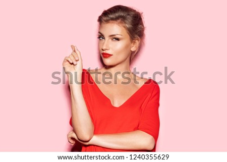 Portrait of beautiful blonde model thinking about great idea and pointing finger on pink background. Fashionably dressed female wearing impressive makeup and looking at camera