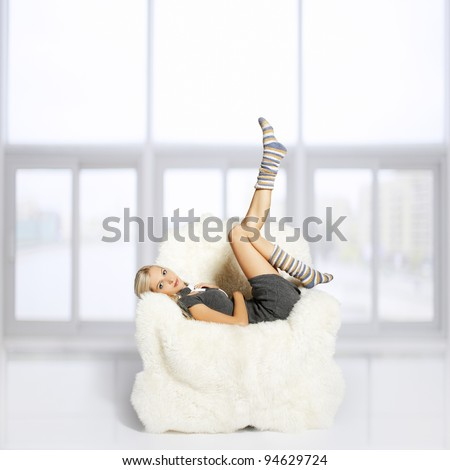 portrait of beautiful blonde sitting on big white furry arm-chair and putting on long striped socks