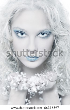 Portrait of beautiful blonde winter snow queen blowing snow flakes from hands
