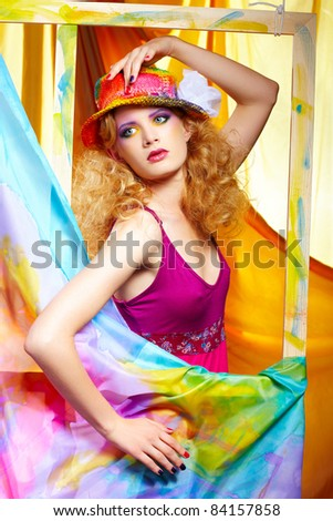 portrait of beautiful blonde woman artist in colorful hat standing behind the easel with painted cloth on it