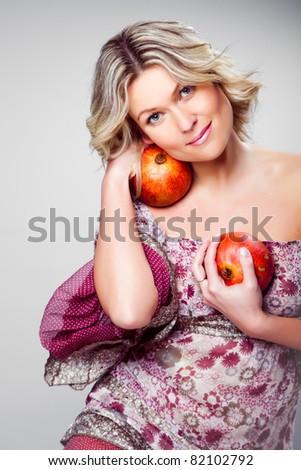 Portrait of beautiful blonde woman holding two pomegranates on grey background - stock photo