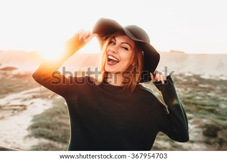 Portrait of beautiful blonde young woman in glasses and holding hat and winking on the beach with sunset light.