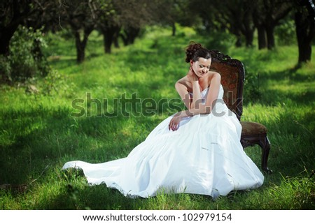 Portrait of beautiful bride sitting on the retro char outdoors