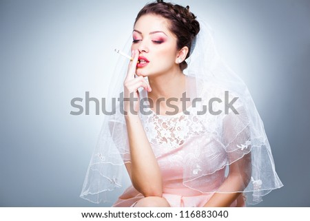portrait of beautiful bride smoking a cigarette - funny picture