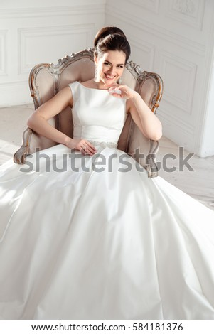 portrait of beautiful brunette bride with elegant hairstyle and makeup wearing long luxury wedding dress #584181376