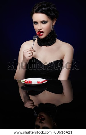 portrait of beautiful brunette girl posing with fork and single red hot spicy cayenne on white plate
