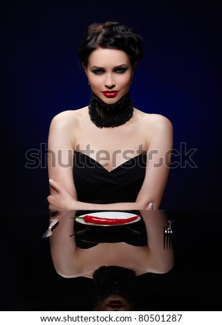 portrait of beautiful brunette girl posing with fork, knife and single red hot spicy cayenne on white plate
