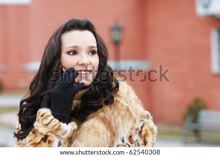 portrait of beautiful brunette in furs speaking over cellphone outdoors