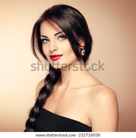 Portrait of beautiful brunette vogue model evening dressed with fashionable hairstyle and professional makeup. Young pretty Caucasian woman with long hair and naked shoulders posing in studio.
