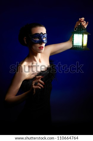 portrait of beautiful brunette woman in carnival mask with shining lamp in hands