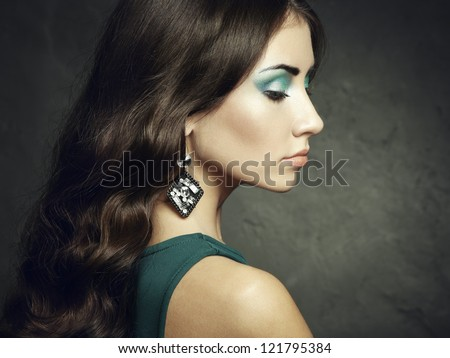 Portrait of beautiful brunette woman in green dress. Fashion photo