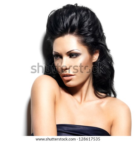 Portrait of beautiful brunette woman with creative hairstyle. Closeup face of fashion model posing at studio about the wall.