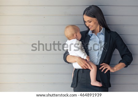 Portrait of beautiful business lady in classic suit and her sweet little baby looking at each other and smiling standing before gray wall #464891939