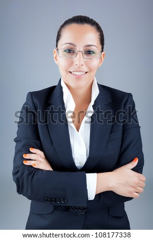 Portrait of beautiful business woman wearing glasses against grey background