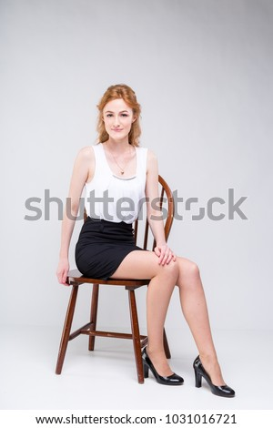 0a2d7b1a0cca Portrait of beautiful business woman with long red, curly hair sitting on  wooden chair on · businesswoman in a blouse and skirt on a white background  ...
