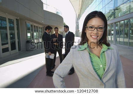 Portrait of beautiful businesswoman with male colleagues in background outside office - stock photo