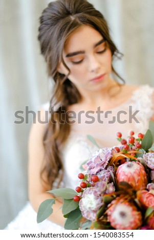 Portrait of beautiful caucasian brunette caucasian bride with bouquet flowers at studio. Concept of bridal photo session and beauty. #1540083554
