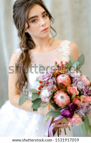Portrait of beautiful caucasian brunette caucasian bride with flowers at studio. Concept of bridal photo session and beauty. #1531917059