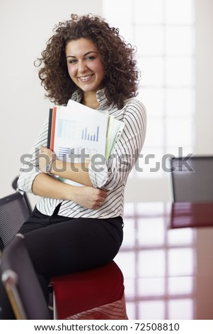 Portrait of beautiful caucasian businesswoman smiling in office, leaning on meeting room table. Vertical shape, front view, copy space