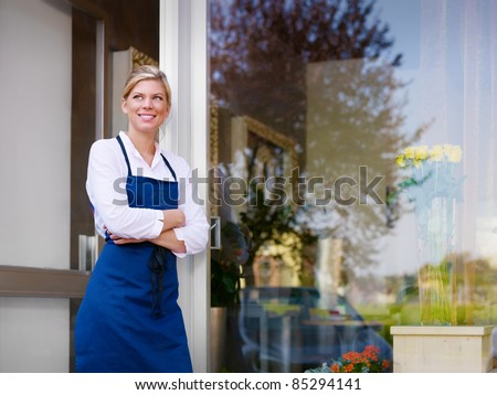 Portrait of beautiful caucasian girl self-employed in flower shop, smiling and looking away. Horizontal shape, waist up, copy space