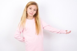 Portrait of beautiful caucasian little girl wearing pink sweater over white background  with arm out in a welcoming gesture.