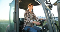 Portrait of beautiful Caucasian young woman in cap sitting in big tractor machine and smiling cheerfully to camera. Pretty happy female farmer worker in field at farm. Agricultural work.