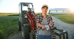 Portrait of beautiful Caucasian young woman in cap standing outdoors a big tractor machine and smiling cheerfully to camera. Pretty happy female farmer worker in field at farm. Agriculture.
