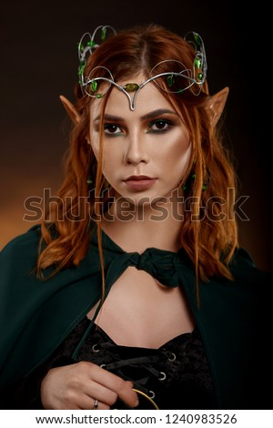 Portrait of beautiful charming girl with silver tiara on her head. Gorgeous elf with red hair in dark green cloak posing at camera and holding her hand near brest. Concept of fairytales and magic.