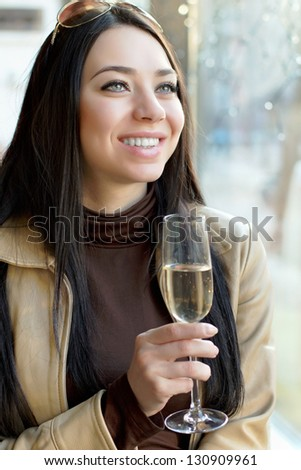 Portrait of beautiful cheerful woman with a glass of champagne. Isolated on white