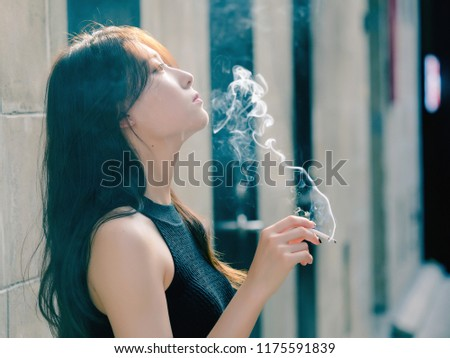 Portrait of beautiful Chinese girl smoking outdoor and thinking about problems, seems a little bit lost, in vintage mode.