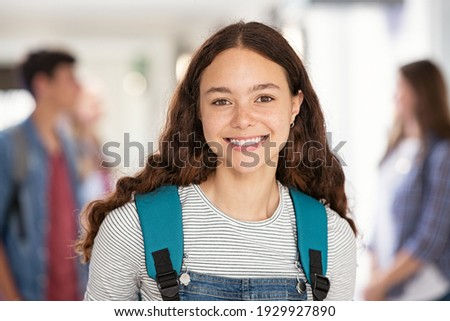 Portrait of beautiful college student standing in hallway school while looking at camera. Intelligent university girl with backpack smiling. Proud and satisfied teen in high school corridor standing.