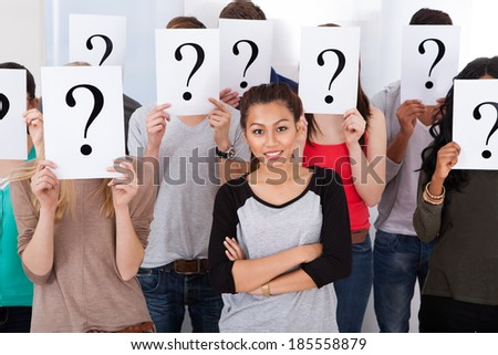 Portrait of beautiful college student surrounded by classmates holding question mark signs in classroom