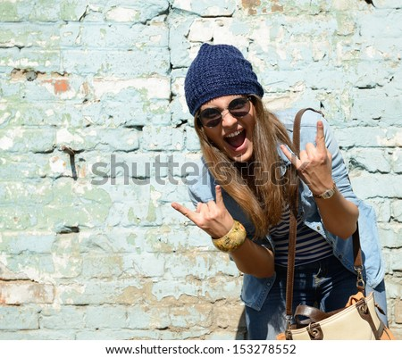 portrait of beautiful cool girl gesturing in hat and sunglasses over grunge wall #153278552