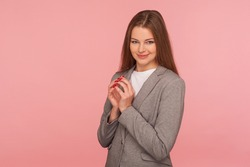 Portrait of beautiful cunning young woman in business suit thinking over devious idea with tricky face expression, scheming and conspiring evil prank. indoor studio shot isolated on pink background
