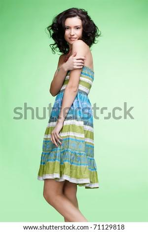portrait of beautiful curly brunette girl in summer dress posing on green - stock photo