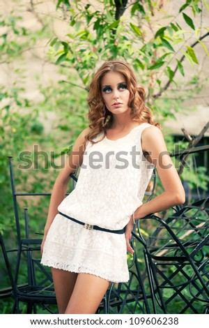 Portrait of beautiful curly young woman wearing white dress in the garden