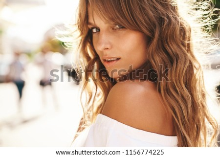 Portrait of beautiful cute smiling blond teenager model without makeup in summer hipster white dress posing on the street background. Turn around #1156774225