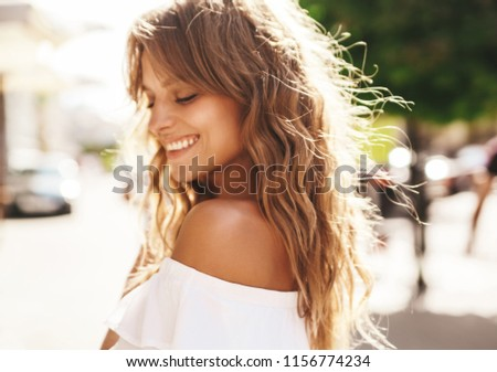 Portrait of beautiful cute smiling blond teenager model without makeup in summer hipster white dress posing on the street background. Turn around