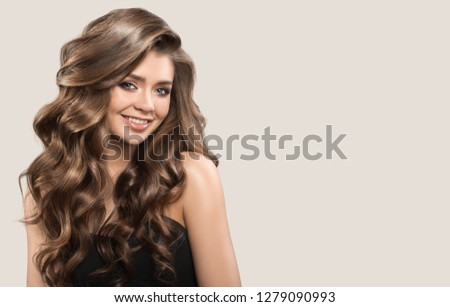 Portrait of beautiful cute woman with curly brown long hair. Gray background. #1279090993