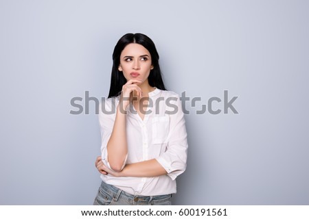 Portrait of beautiful cute young  woman with pouted sensual lips and black hair fink about new idea and looking at something #600191561