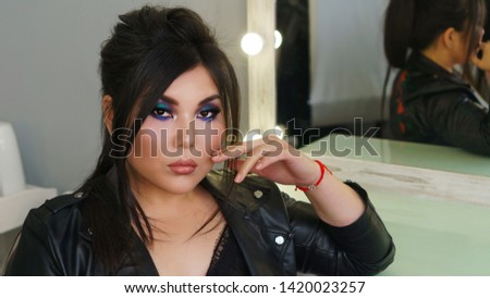 Portrait of beautiful dark haired pan-asian model with perfect make up and stylish hairdo fishbone braid. Plus size model posing sitting by mirror in beauty salon. Beauty industry