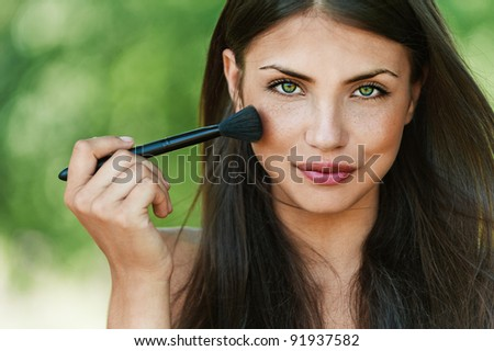 portrait of beautiful dark-haired sexy girls with makeup brush in hand on green background