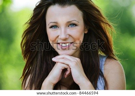 Portrait of beautiful dark-haired smiling girl propping up her face at summer green park.