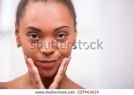 Portrait of beautiful  dark skinned girl being  puffed up touching her cheeks   looking at camera  isolated on white background  with copy place