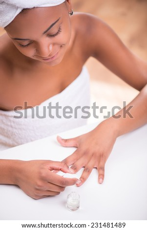 Portrait of beautiful  dark skinned girl in white towel on head and body painting her nails with transparent enamel looking at hands sitting at white table
