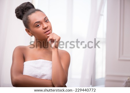 Portrait of beautiful  dark skinned girl in white towel with black curly hair in bun thinking  and touching chin looking at camera isolated on white background  with copy place
