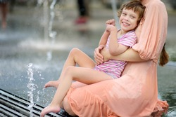 Portrait of beautiful disabled girl in the arms of his mother having fun in fountain of public park at sunny summer day. Child cerebral palsy. Inclusion.