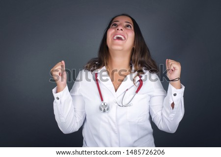 Portrait of beautiful doctor woman looks with excitement up, keeps hands raised, notices something unexpected, poses outdoors. Lovely woman reacts on sudden news