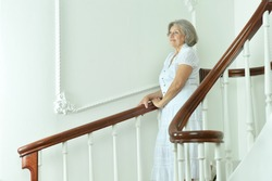 Portrait of beautiful elderly woman on stairs with railing